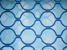 Blue Metal Scrollwork in Shop Window. Blue Metal decorative grill in a shop window Royalty Free Stock Photos