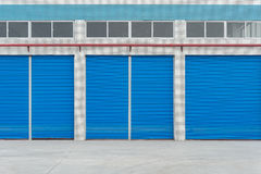 Blue metal shutter doors on commercial shop. Front royalty free stock images