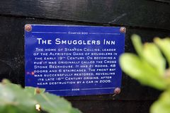 The Smugglers Inn sign in Alfriston. This is the blue metal sign about the smugglers Inn Alfriston, Sussex. Situated in the village centre, this cosy inn dates stock photos