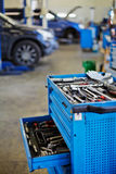 Blue metal tool cabinet with open case at service station. Shallow dof stock image
