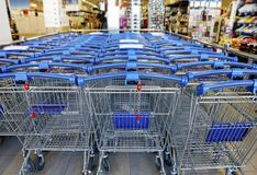 Blue metalic shopping carts in a supermarket, DOF. royalty free stock image