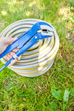 Blue metall spanner and plastic hose Stock Photography