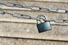 Blue metallic padlock hangs on silver iron chain Stock Images