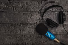 Blue microphone with black wire and black headphones on black wooden table. Equipment for conferences, music studios and meetings. Blue microphone with black royalty free stock photo