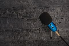 Blue microphone with black wire on black wooden table. Equipment for conferences, music studios and meetings. Blue microphone with black wire on black wooden stock photo