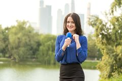 Blue microphone in the hands of a reporter Royalty Free Stock Photography