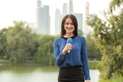 Blue microphone in the hands of a reporter Stock Photography