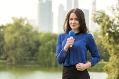 Blue microphone in the hands of a reporter Stock Image