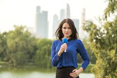 Blue microphone in the hands of a reporter Royalty Free Stock Photo