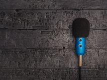 Blue microphone with wire on black wooden table. Equipment for conferences, music studios and meetings. Blue microphone with wire on black wooden table. The view stock photos