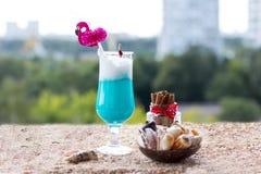 Blue milkshake. Yellow sand and sea shells stock images