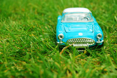 Blue miniature car on grass. Blue miniature toy car on grass. Low depth of field royalty free stock image
