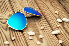 Blue mirrored sunglasses and shells on the wooden background clo Stock Photo