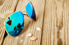 Blue mirrored sunglasses wiht reflection of martini glass on the Stock Photo