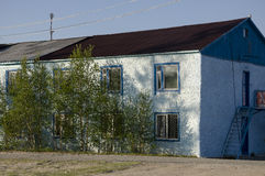 Blue misery and poor two-storeyed building with trees around.  Royalty Free Stock Photos