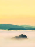 Blue misty morning, view over rock  to deep valley full of light mist. Dreamy spring landscape within daybreak Royalty Free Stock Image