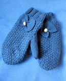 Blue Mittens. Blue wool mittens with a decorative bow on a blue background Stock Photography