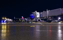 Blue modern aircraft maintenance night airport , fuel truck, jet bridge and the staff people. Completely white passenger Royalty Free Stock Photo