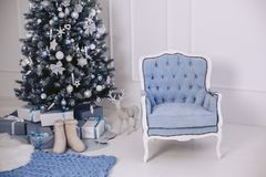 A blue modern elegant chair in the New Year`s interior. Christmas tree with decorations. Gifts in packages. A blue modern elegant chair in the New Year`s Stock Image