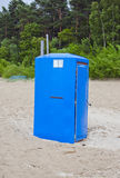 Blue modern plastic portable toilet in  sandy beach Stock Photos