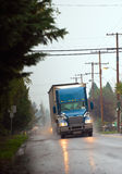 Blue modern semi truck with hightlight on raining road Royalty Free Stock Photography