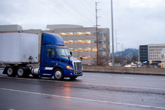 Blue modern semi truck with trailer on wet highway Stock Photography
