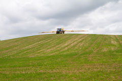 Blue modern tractor pulling a crop sprayer on a hill Royalty Free Stock Photography