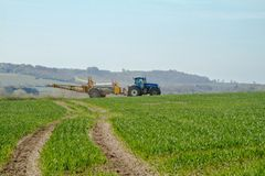 Blue modern tractor pulling a crop sprayer Royalty Free Stock Photos