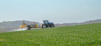 Blue modern tractor pulling a crop sprayer Royalty Free Stock Photo