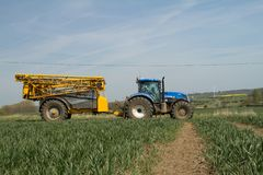 Blue modern tractor pulling a crop sprayer Stock Photo