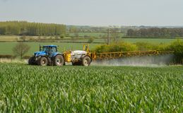 Blue modern tractor pulling a crop sprayer Stock Images