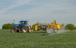 Blue modern tractor pulling a crop sprayer Stock Photos