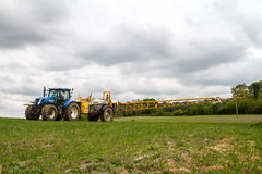 Blue modern tractor pulling a crop sprayer Stock Image