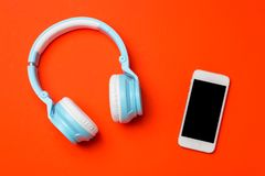 Blue modern wireless headphones with a mobile phone on red orange background. Listening to music concept. Stock Photos