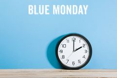 Blue Monday words on blue colored background with clock. Blue Monday text on blue colored background wall with black clock on wooden desk stock photo