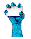 Blue Monster Hand. As a zombie holding a blank sign card as a creepy halloween or scary alien symbol with textured cold skin and hairy wrinkled fingers on a Stock Photos