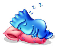 A blue monster sleeping above a pillow Royalty Free Stock Photography