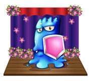 A blue monster at the stage holding a shield Royalty Free Stock Images