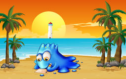 A blue monster writing at the beach Royalty Free Stock Photography
