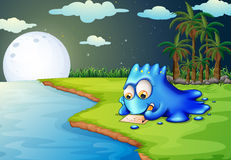 A blue monster writing a letter at the riverbank Royalty Free Stock Photo