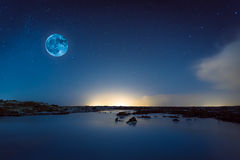 Blue moon. A Blue moon hanging in the sky above the Blue Lagoon, Iceland on a starry night Royalty Free Stock Photos