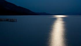 Blue moon reflected on the ocean Stock Photos