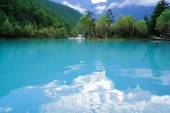The blue lake reflects the blue sky and white clouds royalty free stock image
