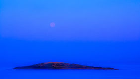 Blue moonset and sunrise. Over small island in Mallorca, Balearic islands, Spain Stock Images