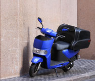 Blue moped motorcycle on city pavement Royalty Free Stock Images