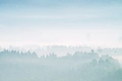 Blue morning. Hills and forests  lines in mountain valley during autumn sunset. Natural mountain landscape in cold mist Royalty Free Stock Images