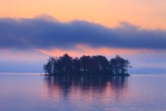 Blue morning lake. Early morning sunrice at the forest lake with small island, red colors in the sky Royalty Free Stock Photos
