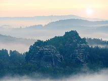 Blue morning, view over rock and fresh green trees to deep valley full of light mist. Dreamy spring landscape. Within daybreak after rainy night. Blue pink sky Stock Photos