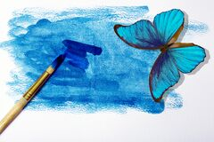 Blue morpho butterfly on a blue background. watercolor paper and blue watercolor paint. wet watercolor paper and brush. watercolor