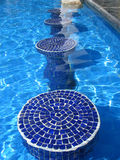 Blue mosaic pool seats. In glistning calm pool royalty free stock photo